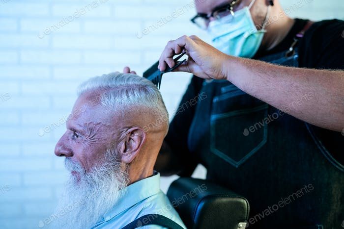Male hairdresser cutting hair to beard senior client while wearing face surgical mask