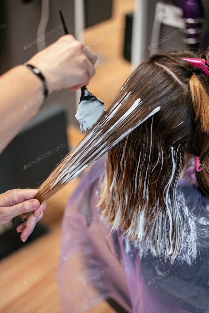 Hairdresser dyeing a woman's hair