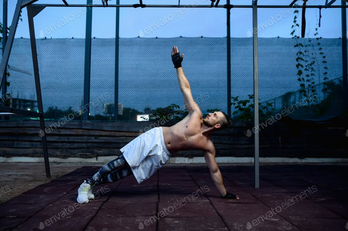 Strong man doing stretch exercise, street workout