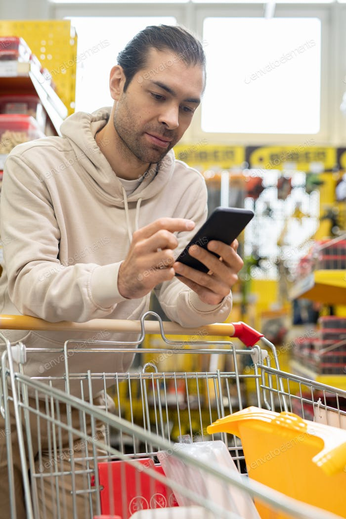 Male consumer with smartphone and shopping cart