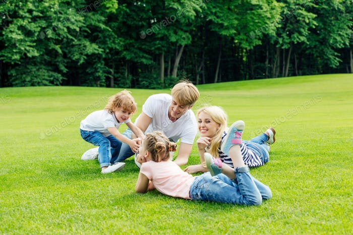 happy young family with two cute children resting together on green grass in park