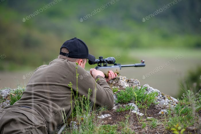 Male with a gun in hunting period
