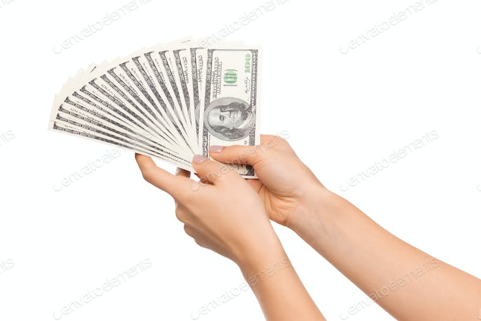Successful investment. Fan of dollar banknotes in female hands