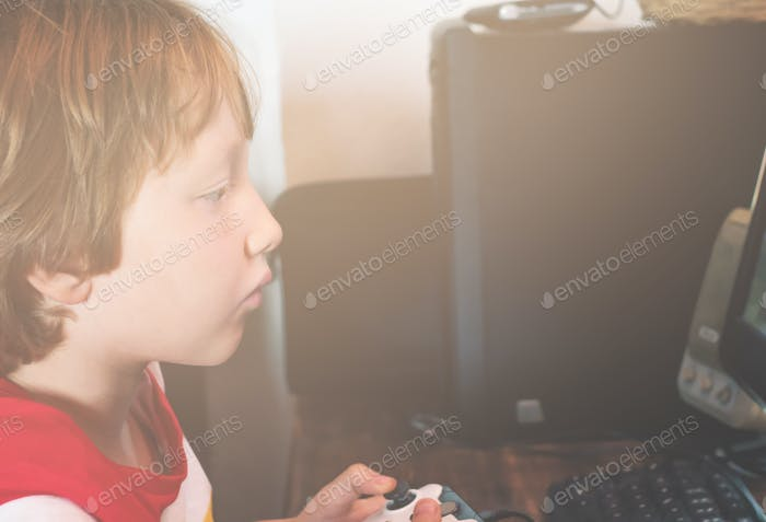 Little kid playing with joystick in front of PC