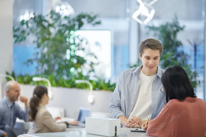 Young Man Talking to Receptionist in College