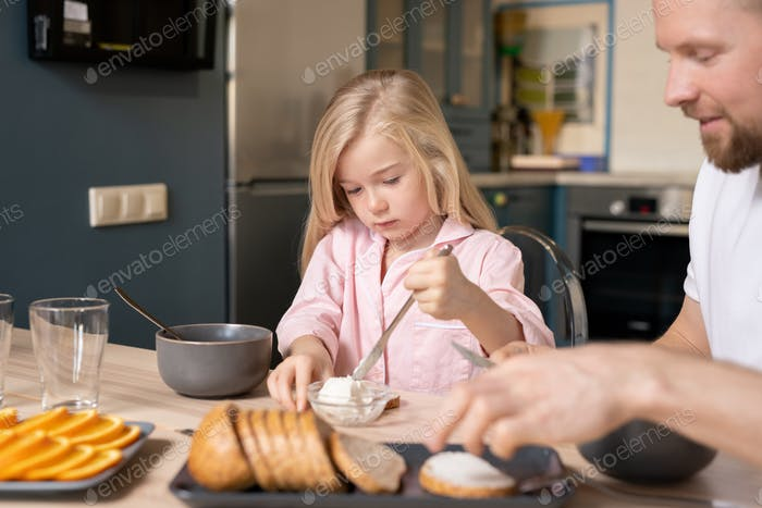 Little girl taking fresh butter to put it in bowl with porridge during breakfast
