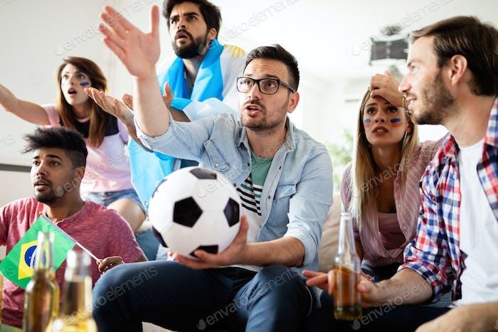 Gruppe von Fußballfans enttäuscht und glücklich beobachten ein Fußballspiel auf der Couch
