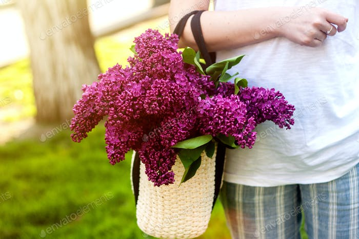 Stylish woman holding straw bag with a vivid bunch of lilac flowers.