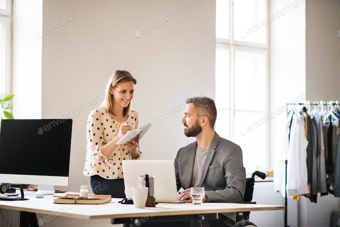 Two business people with wheelchair in the office.