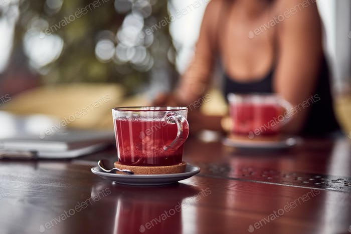 Close up view of cuo of tea on the table with african american woman sitting at background