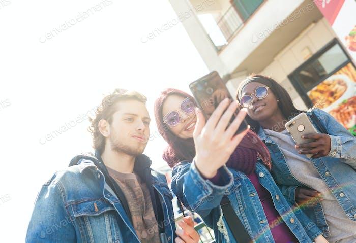 Multirassische Freunde machen Selfie im Freien.