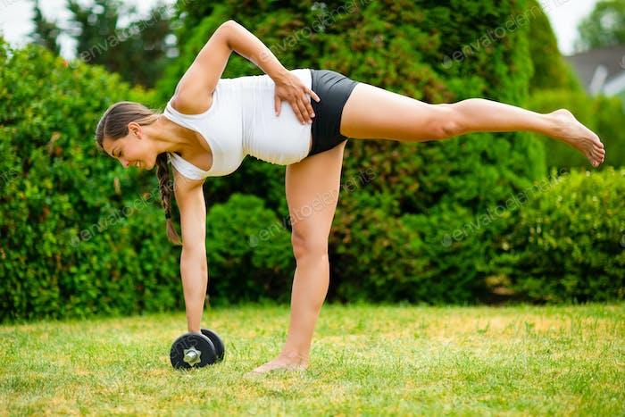 Pregnant Woman Doing Single Leg Dumbbell Deadlift In Park