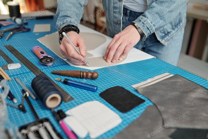 Young leatherworker in workwear outlining paper pattern over piece of suede