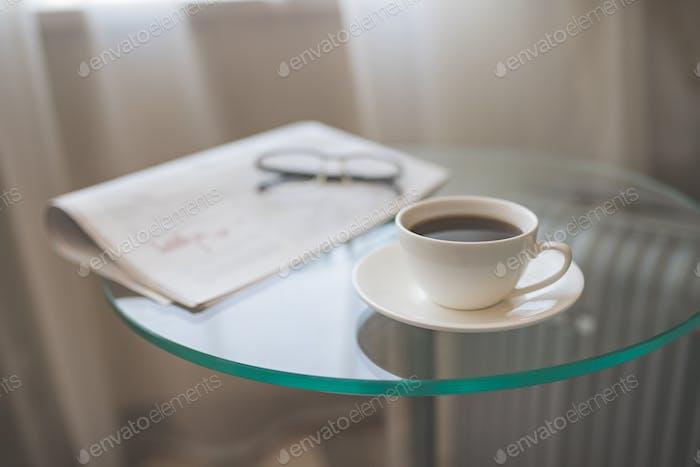 Una taza de café con un periódico