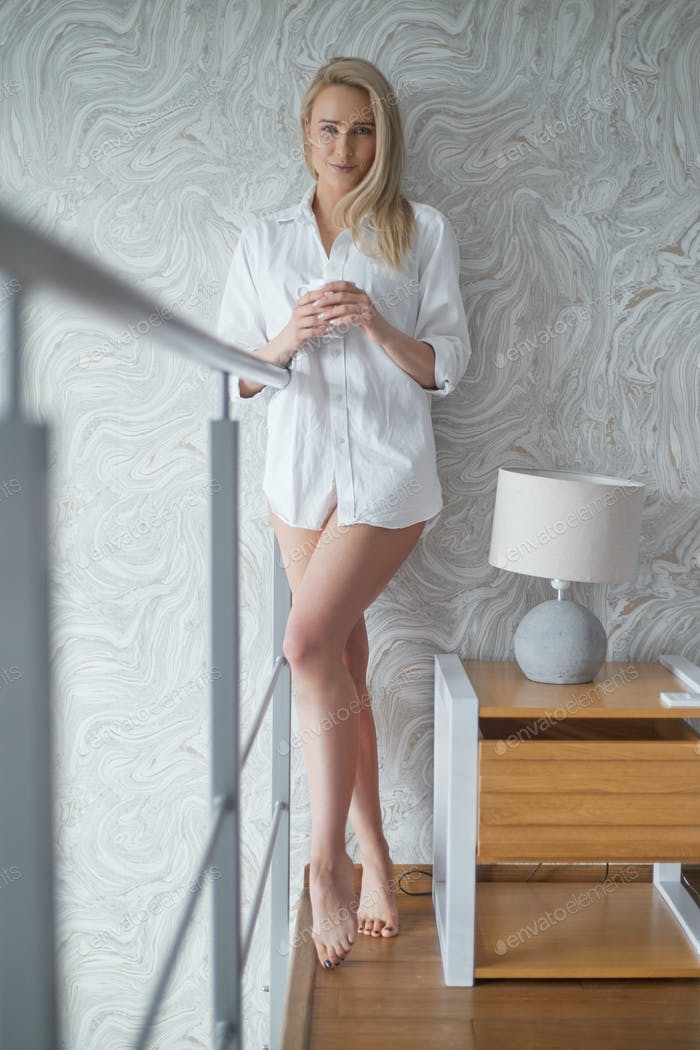 Beautiful blonde woman standing next to a window in a loft apartment