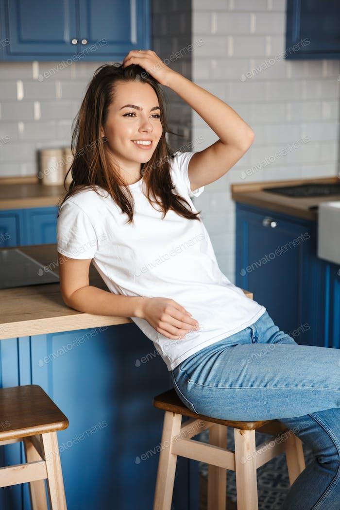 Bild von fröhlich schöne Frau lächelnd während des Sitzens