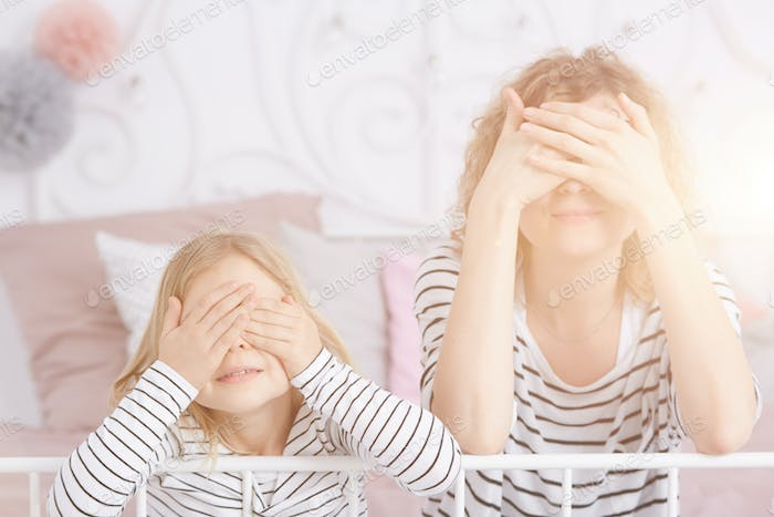 Girl and mom covering eyes