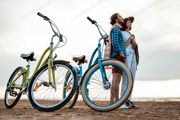 Two people are standing on the beach with blue and green bikes