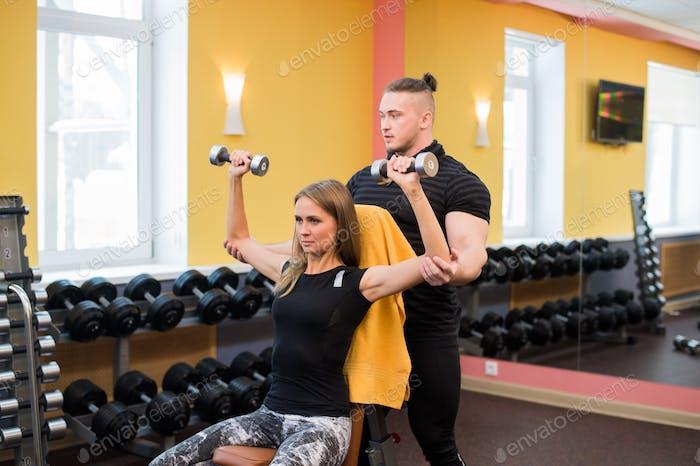 Frau mit ihrem persönlichen Fitnesstrainer in der Turnhalle trainieren Kraftgymnastik mit einer Langhantel