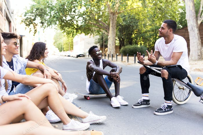 Group of young hipster friends talking in an urban area.