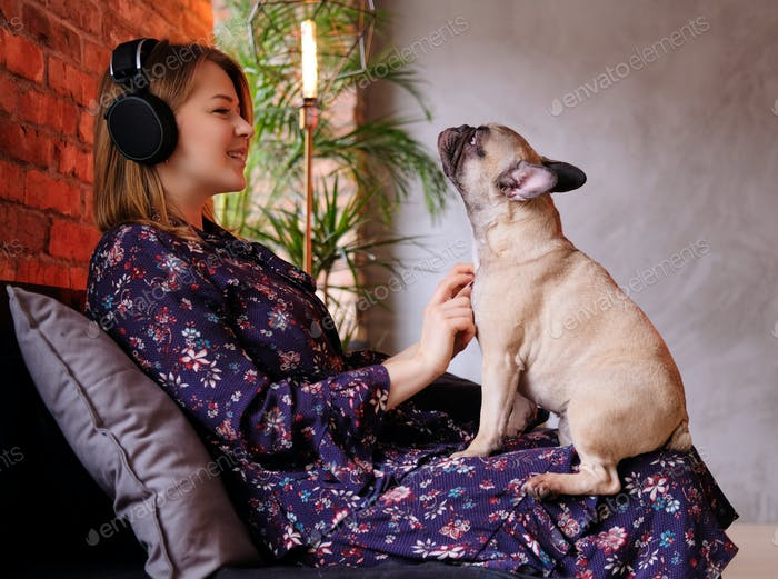 Happy blonde woman in dress sitting with her cute pug on a handmade sofa and listening to music