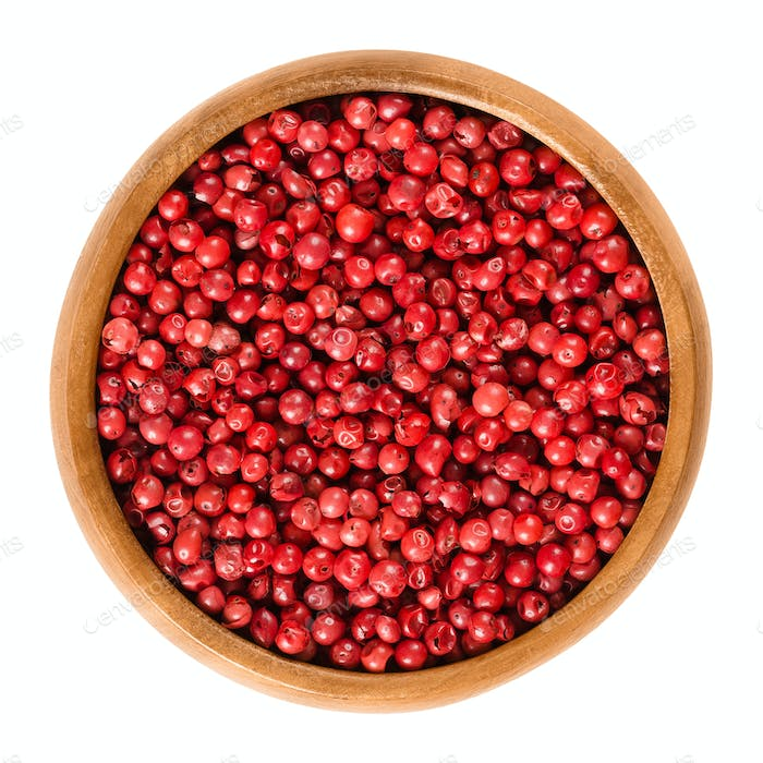Pink pepper in wooden bowl over white