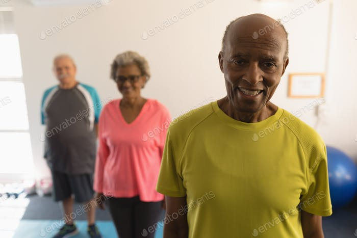 Front view of happy senior friends looking at camera in fitness studio