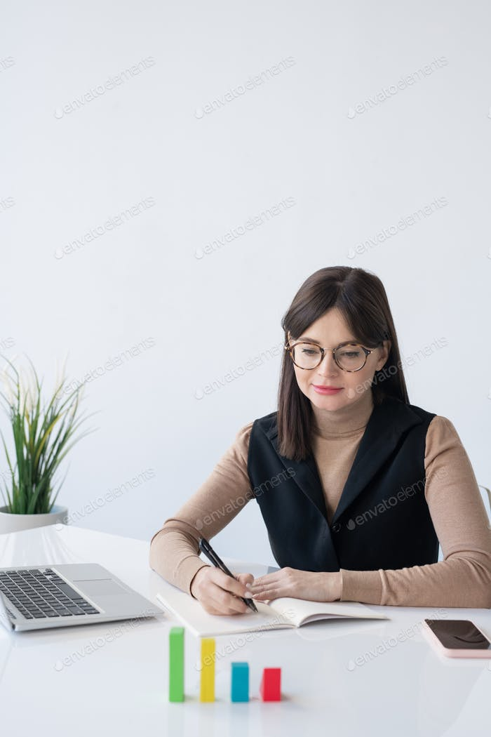 Young elegant female broker looking at multi-color cube chart on desk