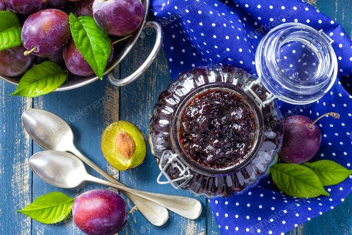 Pflaumenmarmelade in einem Glas und frische Früchte mit Blättern