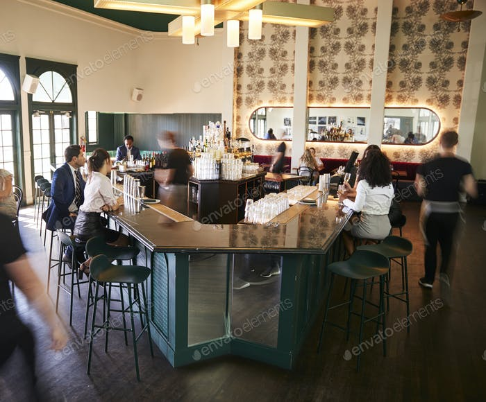 Interior Of Busy Cocktail Bar In Restaurant With Staff Serving Customers