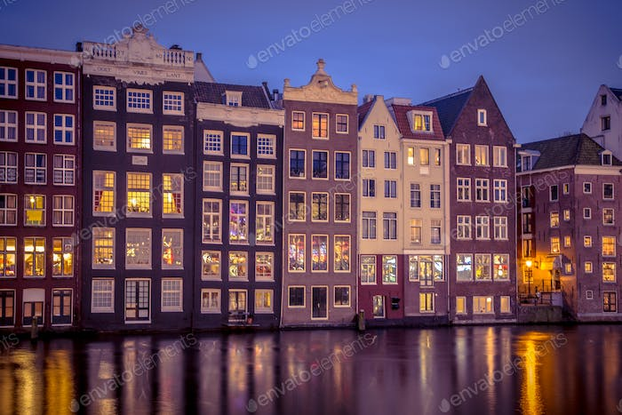 Night shot ofCanal houses on Damrak in Amsterdam