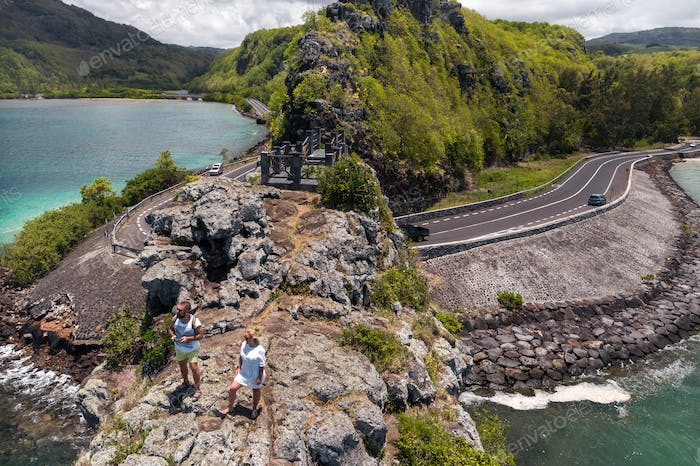 The couple stands on the edge of a cliff on the island of Mauritius.An unusual road to the islands