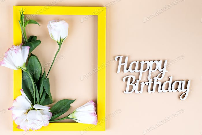 Empty yellow frame, Happy Birthday letter and flowers eustoma on beige paper background with copy