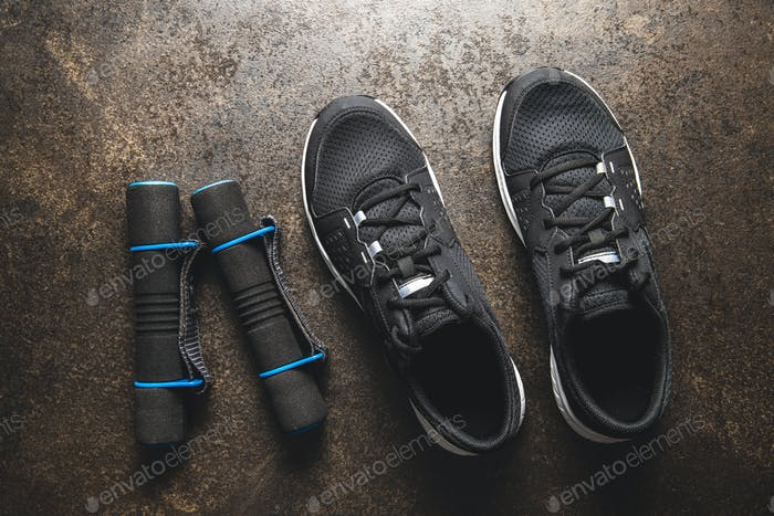 Fitness concept. Black sports shoes and dumbbells.