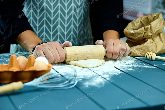 Baker hands preparing fresh dough with rolling pin on kitchen table