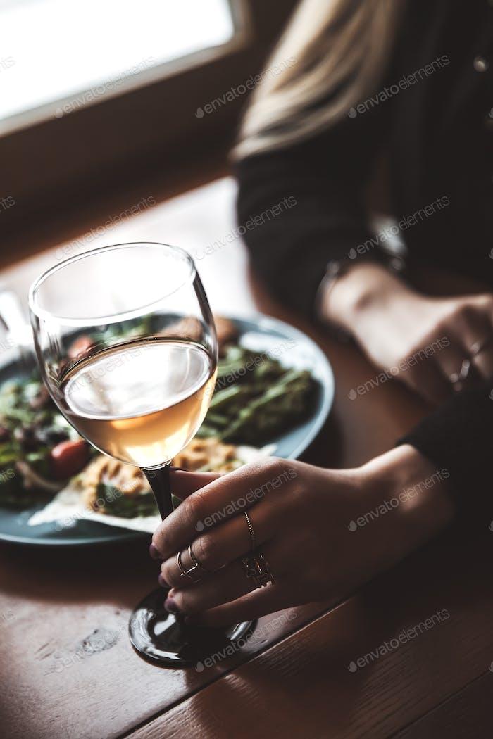 Weibliche Hand mit Glas Wein und Essen im Hintergrund