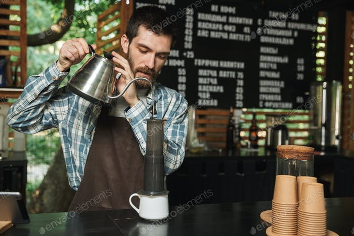 Portrait of caucasian barista man making coffee while working in