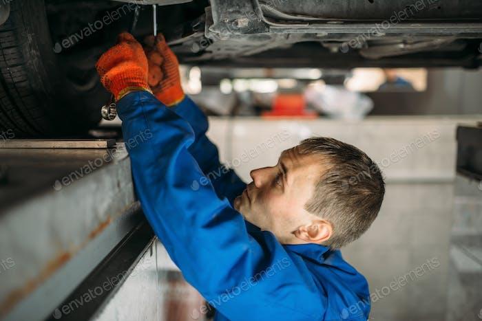 Mechanic adjusts the wheel angles on stand