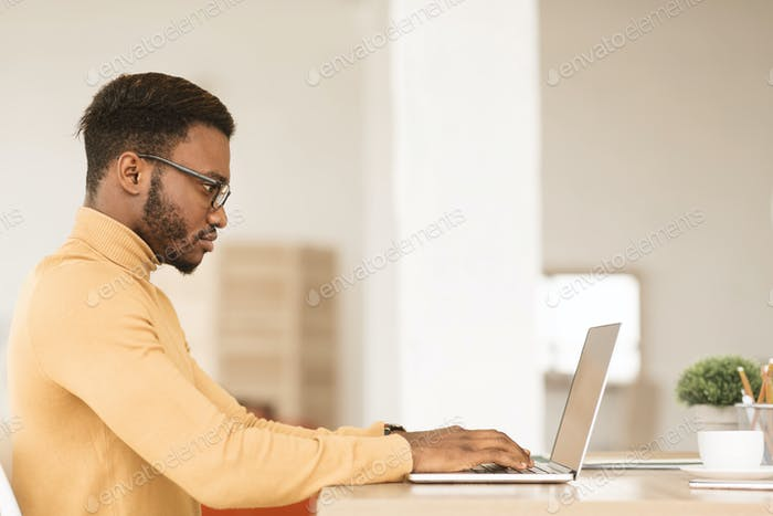 Afro guy working on his laptop at home