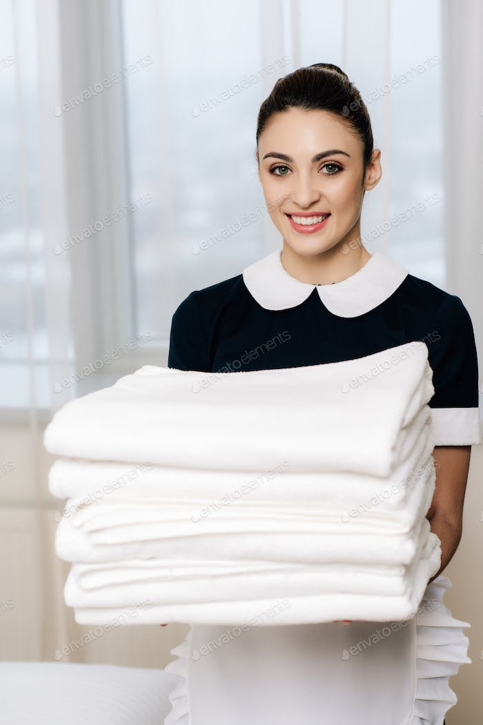 young happy maid in uniform holding stack of clean towels and looking at camera