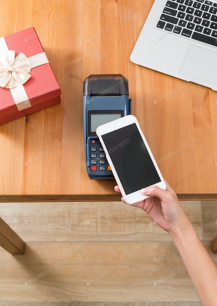 Bezahlen Sie mit Handy auf POS-Maschine für Gegenwart