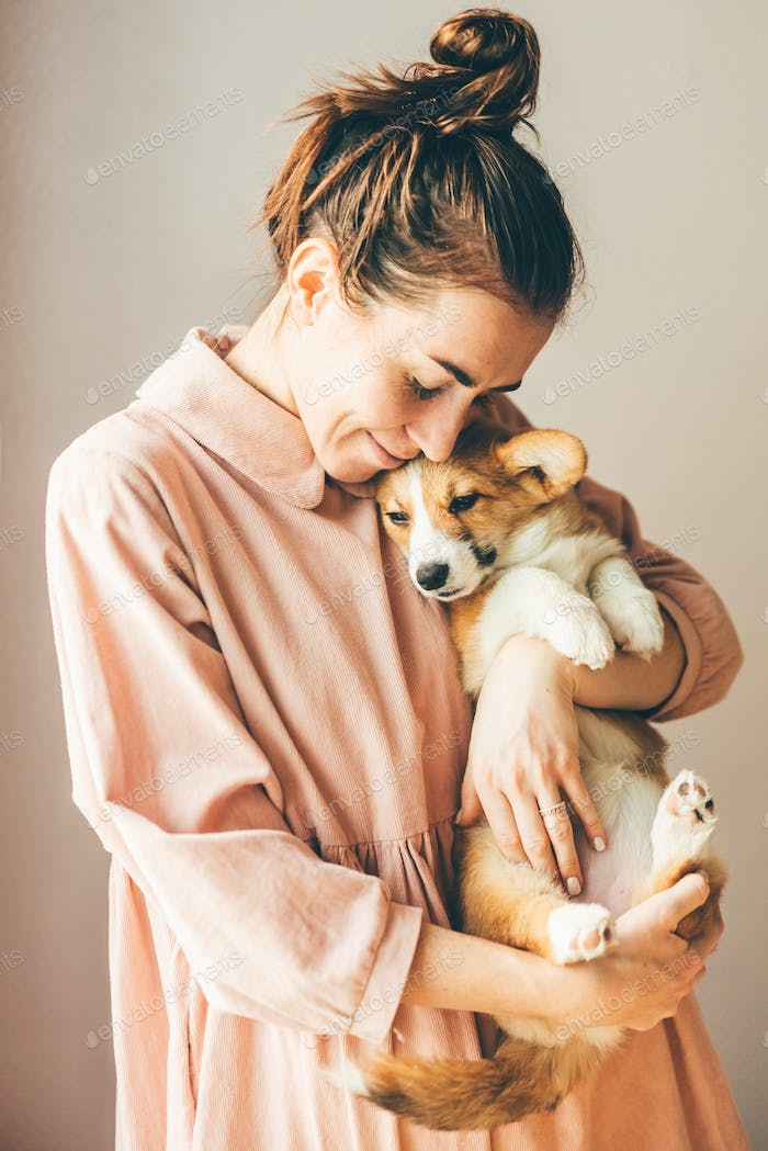 Smiling young woman embracing corgi pappy with closed eyes.