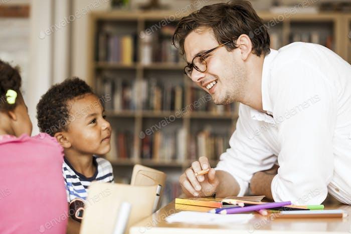 Profesor masculino feliz enseñando a los estudiantes durante la clase de arte