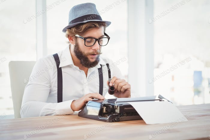 Hipster holding smoking pipe while working on typewriter at desk in office