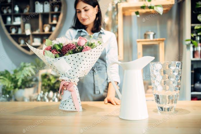 Florist schaut auf Blumenstrauß im Blumenladen