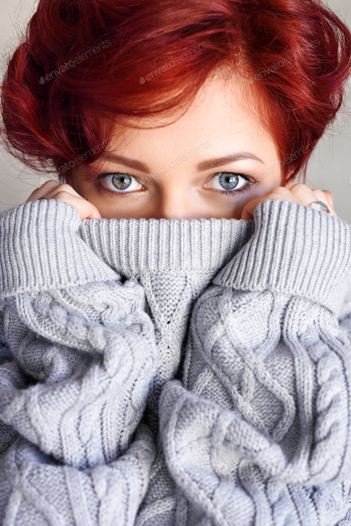 Portrait of a beautiful young red-haired woman with short hair w