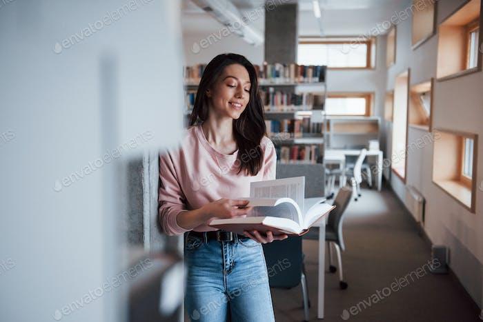 Intellektuelles Wachstum Brünette Mädchen in Freizeitkleidung mit guter Zeit in der Bibliothek voller Bücher