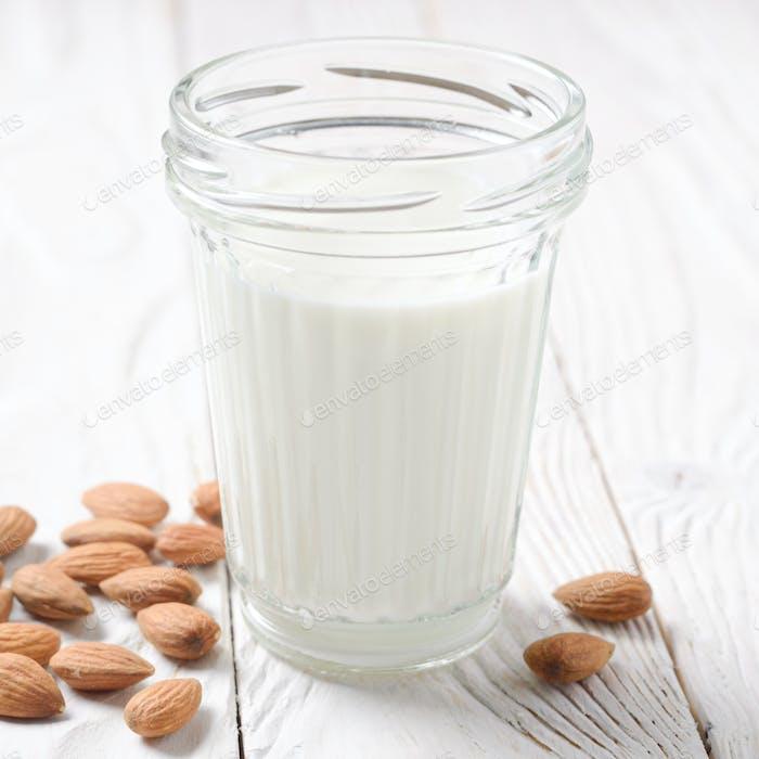 Milch oder Joghurt im Mauerglas auf weißem Holztisch mit Mandeln