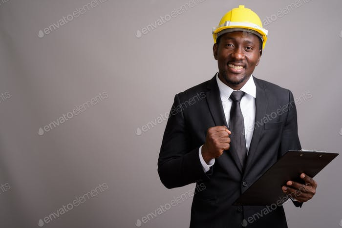Young handsome African businessman with hardhat against gray bac