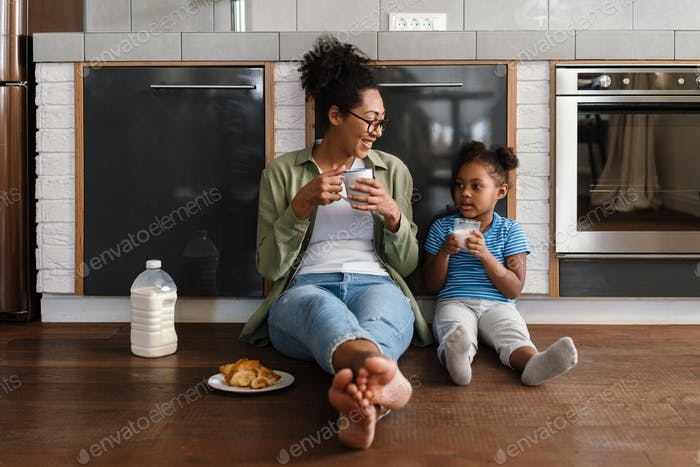 Happy mother sitting on floor with her daughter in home kitchen